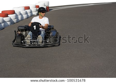 Man racing in a go-kart on the race track - stock photo