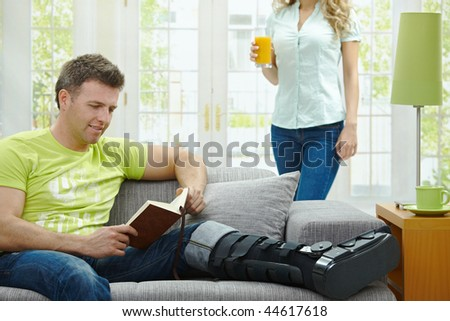Man rasting his broken leg in cast on sofa at home, reading book. - stock photo