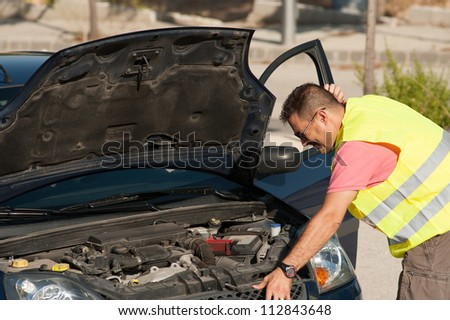 Man rather confused about the reason of his breakdown - stock photo