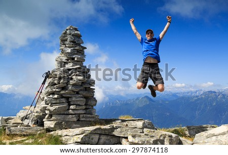 Man reaching the summit and jumping out of joy beside a big cairn on a mountaintop. - stock photo