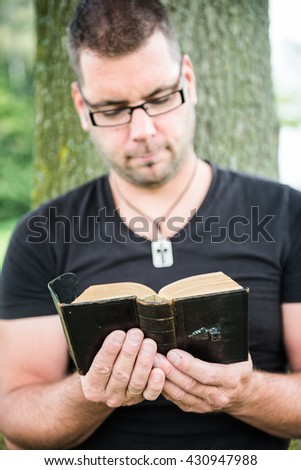 Man reading a bible outside - stock photo