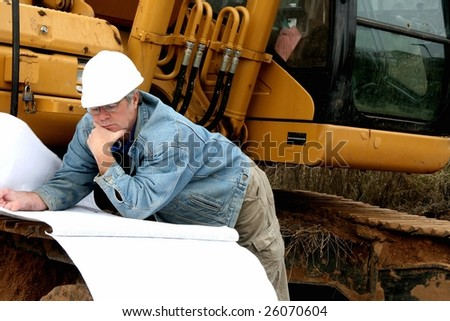 man reading a blueprint near machinery - stock photo
