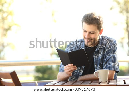 Man reading a book in an ebook reader sitting in a bar or home terrace - stock photo