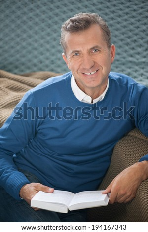 Man reading a book on a sofa