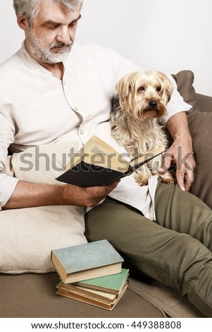 Man reading a book with his lovely dog