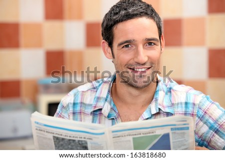 Man reading a newspaper in the kitchen - stock photo