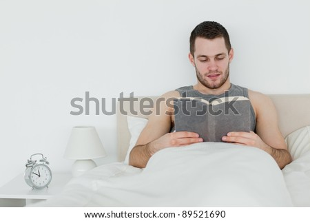 Man reading a novel in his bedroom - stock photo
