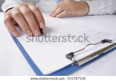Man reading a typed document holding a pen in his hand in readiness for making notes and annotations, close up view of the hands