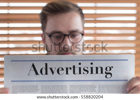 Man reading Advertising headlined newspaper