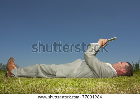 Man reading an ebook in a park - stock photo