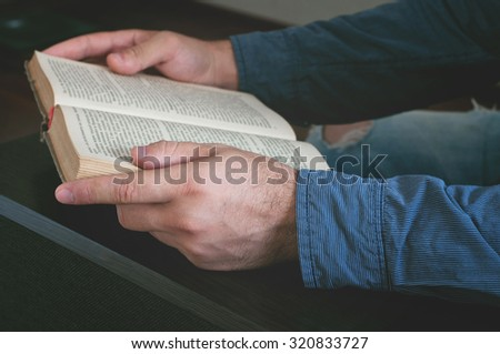 Man reading an old book closeup. Top view