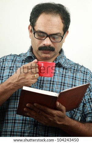 Man reading book and drinking coffee - stock photo
