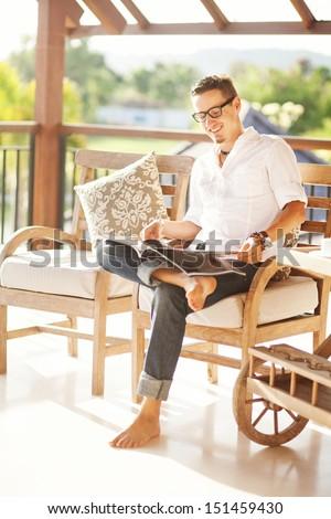 man reading magazine at home - stock photo