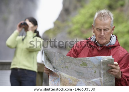 Man reading map with blurred woman looking through binoculars in background - stock photo
