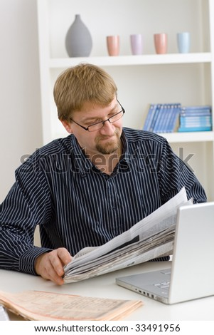 Man reading newspaper at home sitting at table with laptop.