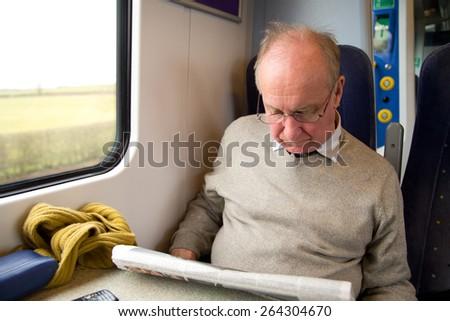 man reading newspaper on the train - stock photo