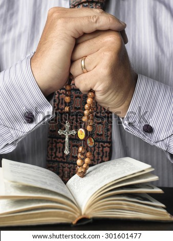 Man reading the bible and praying the rosary
