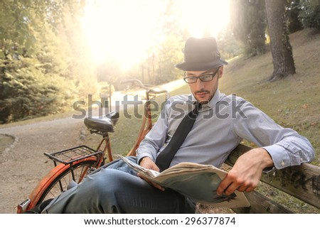 Man reading the newspaper at the park - stock photo