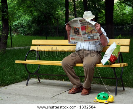 Man reads newspaper. Man in park on yellow bench with turtle. - stock photo