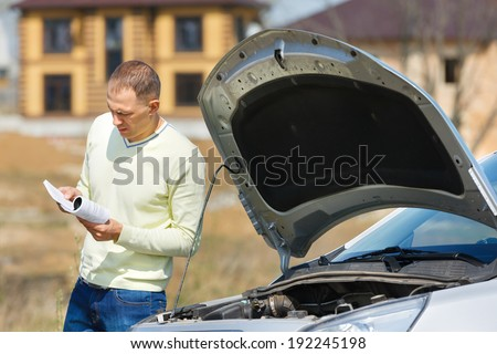 man reads the manual near the car with the hood open - stock photo