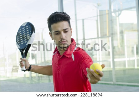 Man ready for paddle tennis serve in outdoors court - stock photo