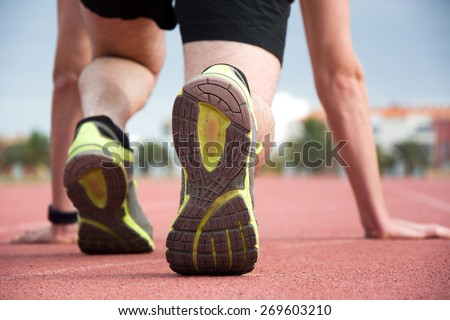 Man ready to run on the track - stock photo