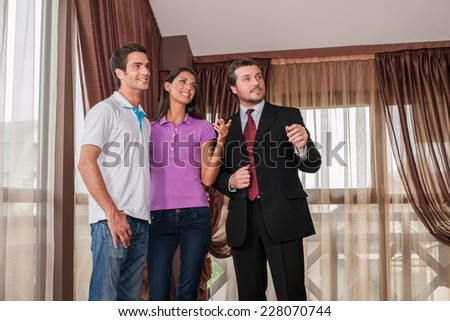 man real estate agent listening to woman client in new house. male agent showing view from new house window - stock photo