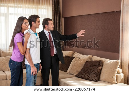 man real estate agent showing couple new house. male agent showing view from window on city - stock photo