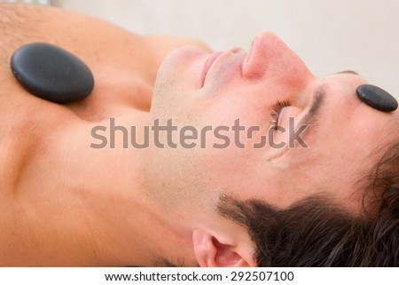 Man receiving a therapy with hot stones - stock photo
