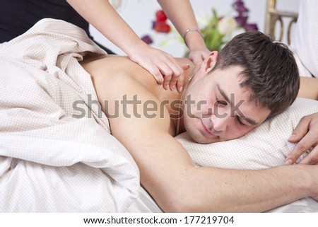 Man receiving domestic massage on bed - stock photo