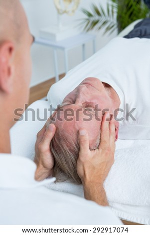 Man receiving head massage in medical office - stock photo