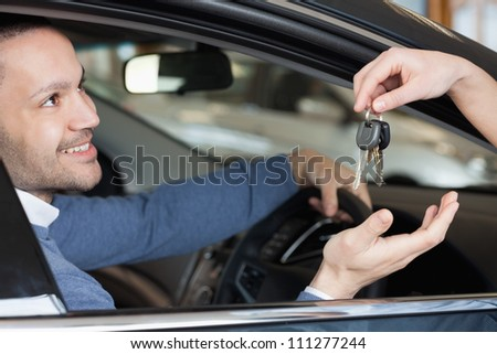 Man receiving keys while sitting in a car - stock photo