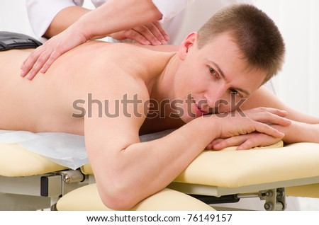 Man receiving massage from doctor in her office - stock photo