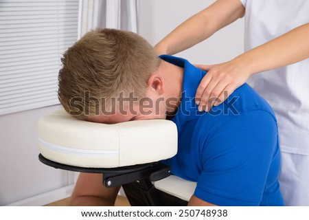 Man Receiving Shoulder Massage From Female Physiotherapist - stock photo