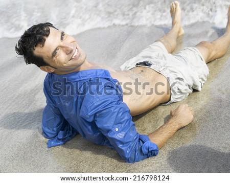 Man reclining on the beach - stock photo