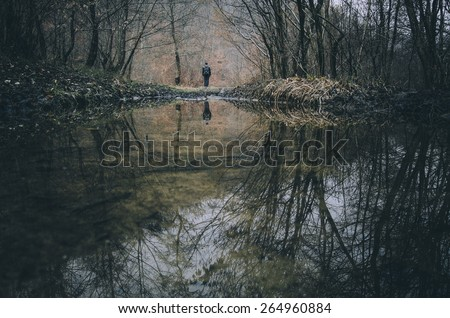 man reflecting in a forest lake fantasy landscape - stock photo