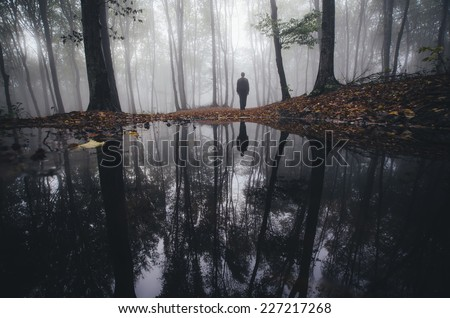man reflection in lake in fantasy forest in autumn - stock photo