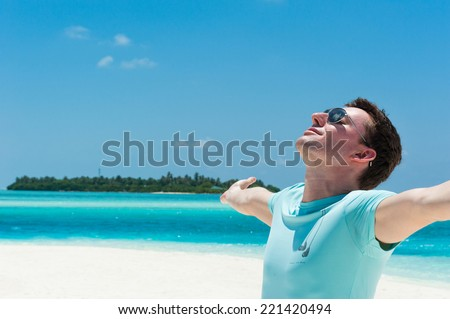 Man relaxing at beach enjoying summer freedom with open arms. Man on summer travel holidays vacation - stock photo