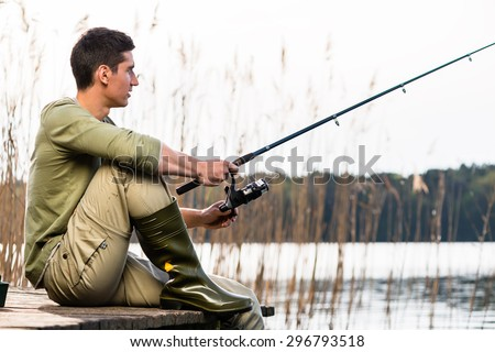 Man relaxing fishing or angling at lake sitting cross-legged on jetty - stock photo