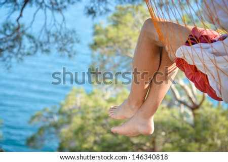 Man relaxing in a hammock on a beautiful sand beach. Cozumel, Mexico, Caribbean Sea. - stock photo