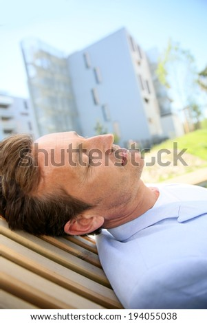 Man relaxing in public park by the city