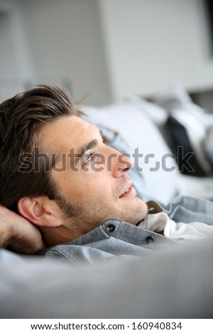 Man relaxing in sofa with arms behind head - stock photo