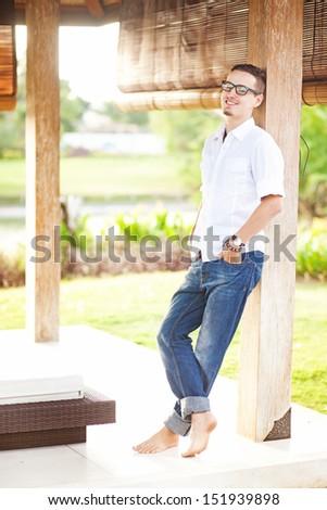 man relaxing near outdoor gazebo in summer - stock photo