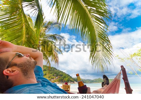 Man relaxing on a tropical beach with a bottle of beer in his hand. - stock photo