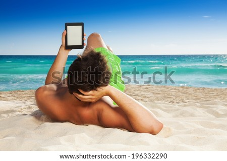 Man relaxing on beach reading e-book - stock photo