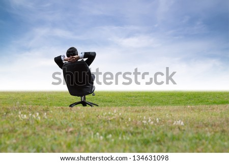 Man relaxing on chair in green meadow. - stock photo
