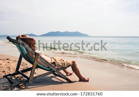Man relaxing on deckchair  - stock photo