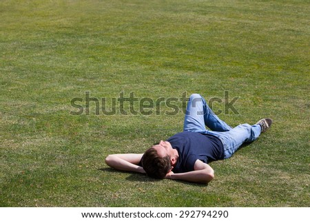 Man relaxing on grass - stock photo