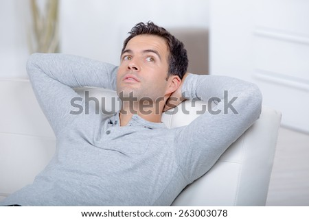 Man relaxing on his sofa - stock photo