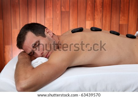 Man relaxing on massage bed with hot stones - stock photo